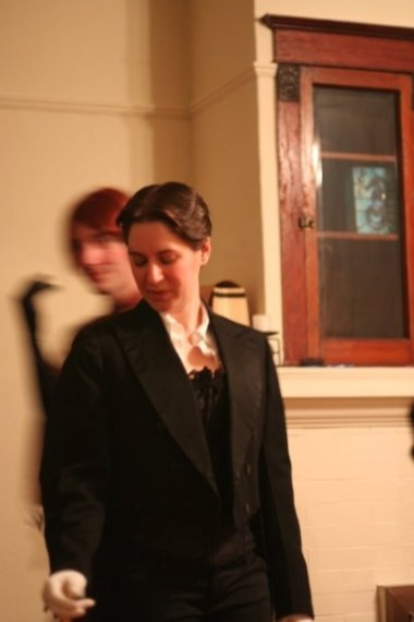 The author pictured looking down, wearing a black tailcoat with white shirt, black jacquard corset, and white gloves.