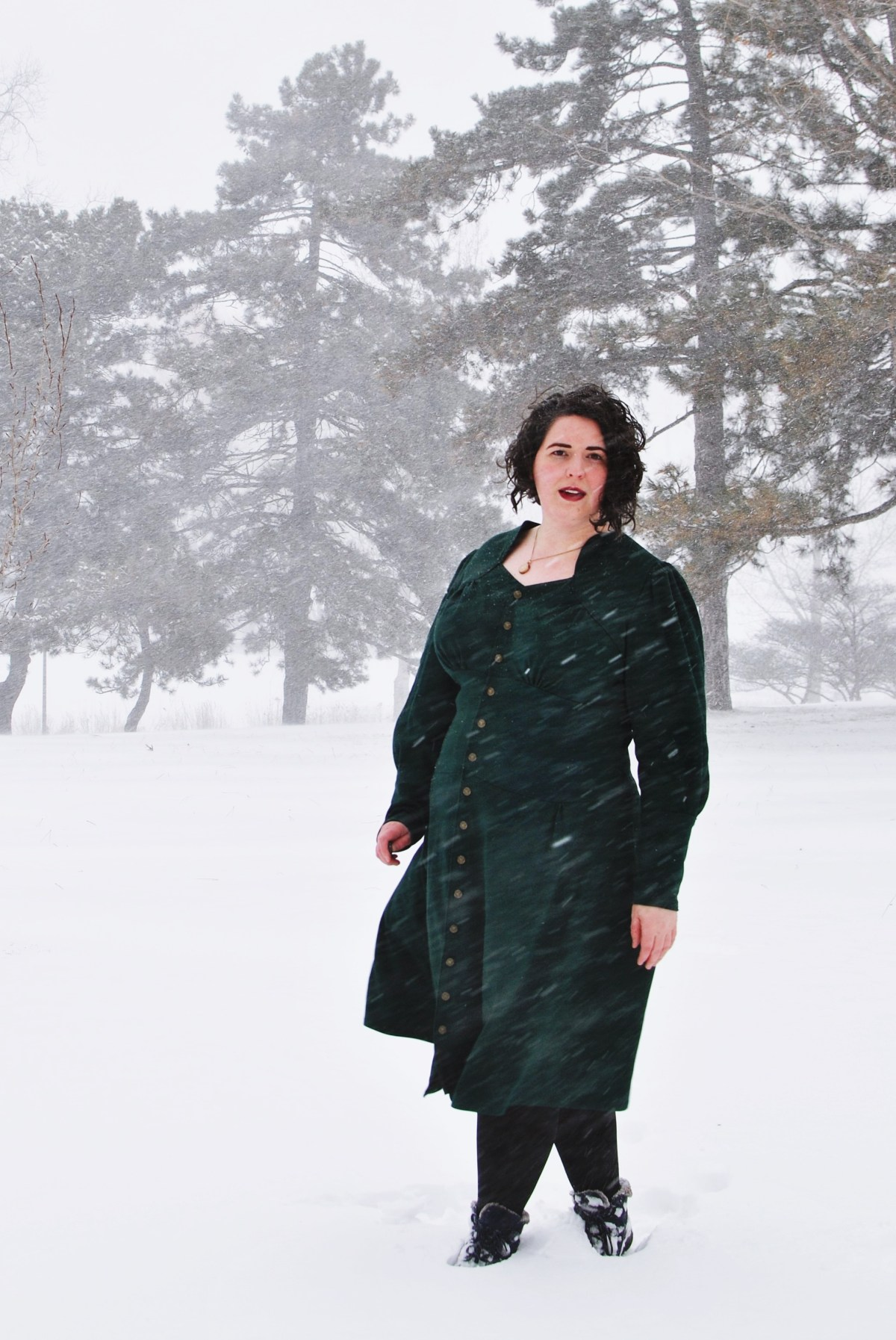 Shannon standing outdoors in blowing snow, wearing a knee-length dark green dress with buttons down the front. The wind blows the skirt of the dress around and snow dots the image.
