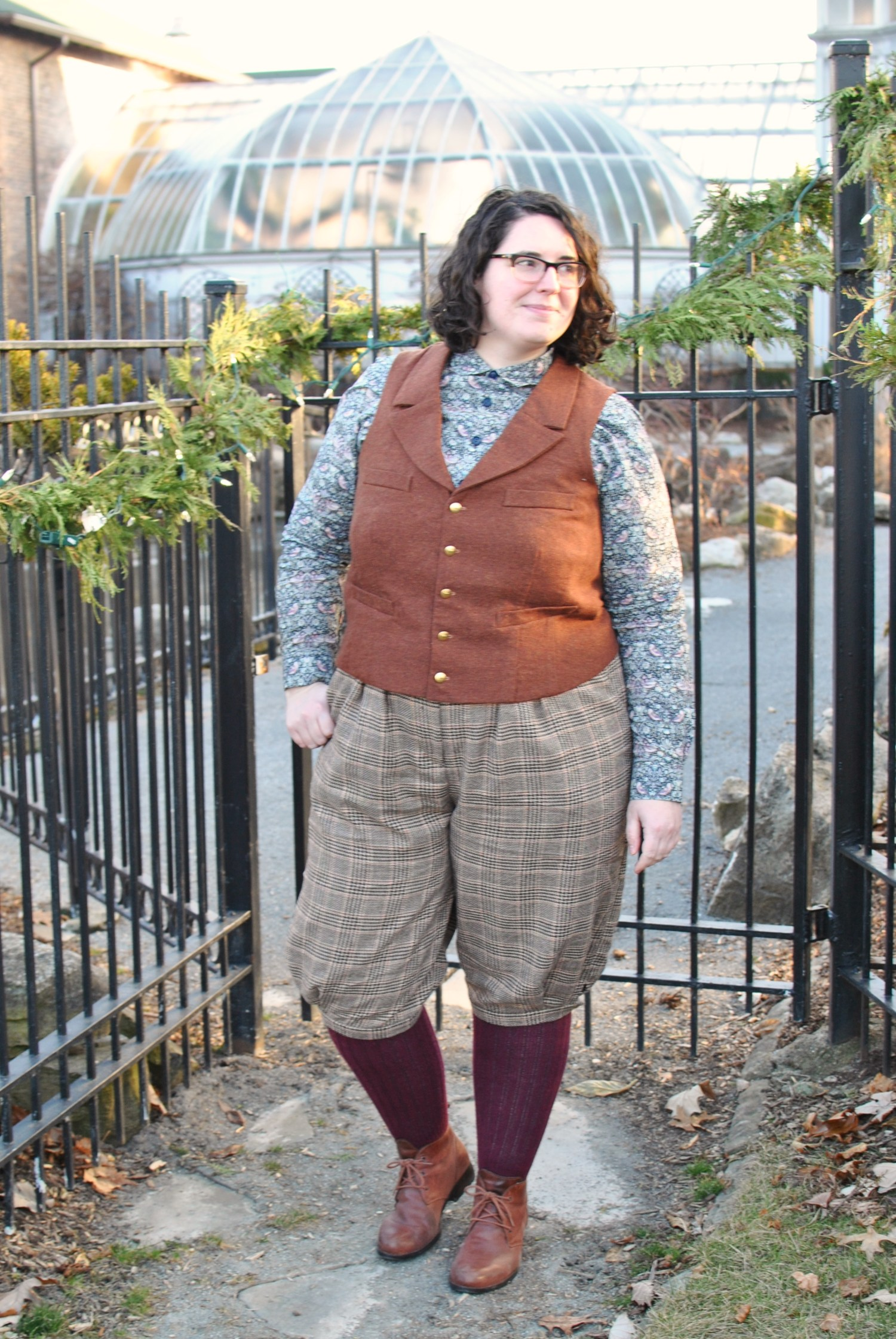 Shannon standing in front of an iron gate, wearing tan knickerbockers, a rust colored vest, a floral shirt, maroon socks, and brown boots.