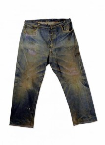 A dark indigo pair of riveted jeans with brown wear lines, pictured flat.