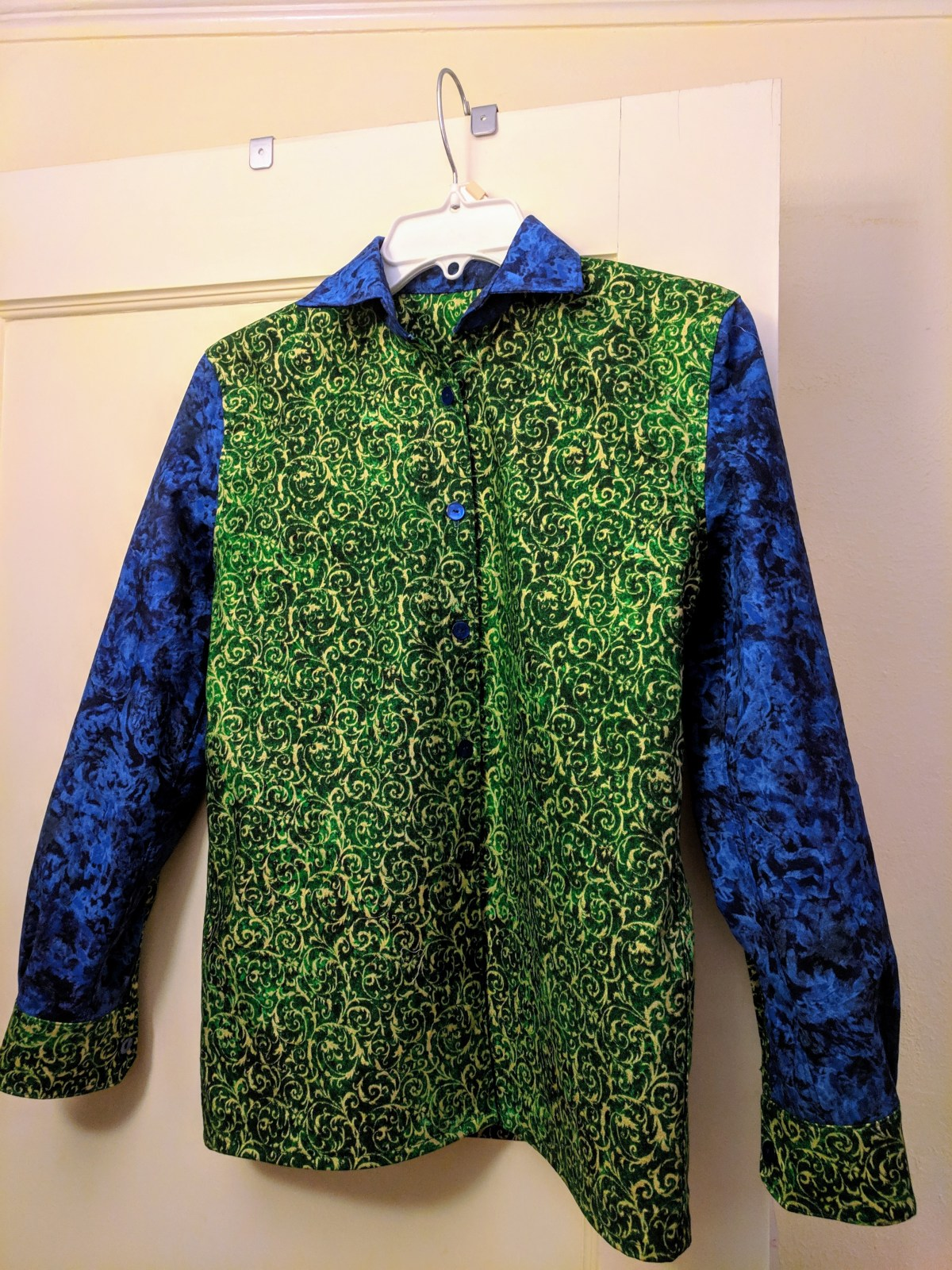 A button-up shirt hangs on a hanger. The shirt has a green body, blue arms, green cuffs, and a blue collar.