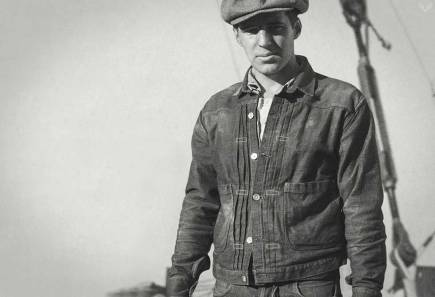 A black and white image of a man in a cap wearing a jean jacket, in front of equipment.