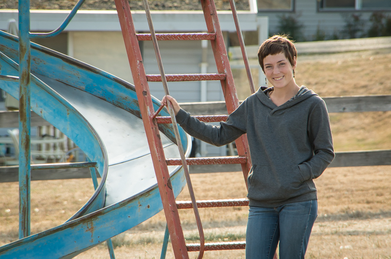 Morgan standing beside a metal slide, wearing a grey Finlayson sweater.