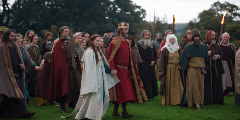 Chris Pine's character wears a long red woollen tunic, a matching gold and red brocade cape, and a golden crown. A crowd of people surrounds him and he holds the hand of the actress playing his character's wife.