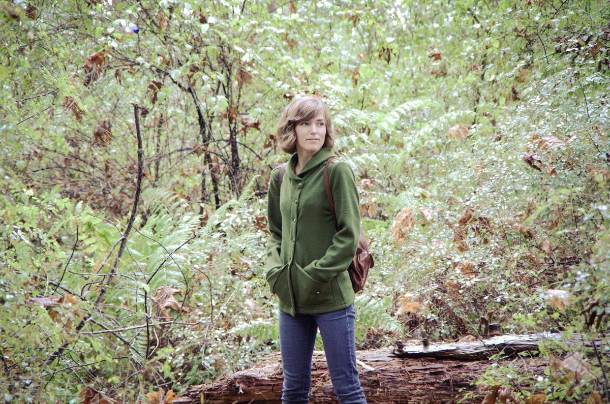 Morgan Meredith standing in a fern gully wearing a green Newcastle cardigan