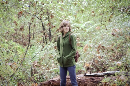 Morgan Meredith standing in a fern gully wearing a green Newcastle cardigan