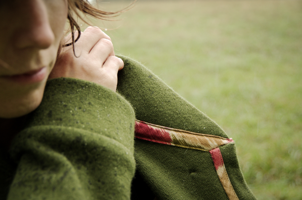 Close up showing colourful bindings on the seams of Morgan's green Newcastle cardigan