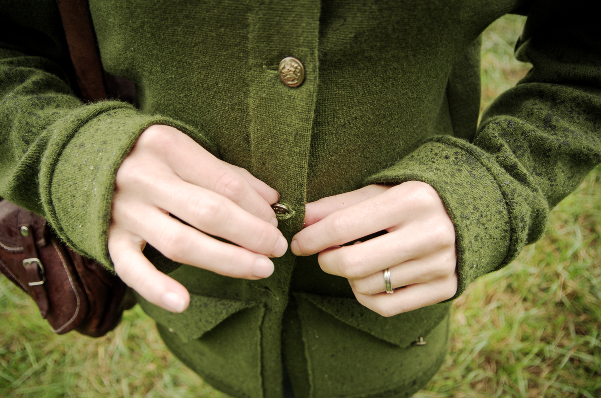 Close up of hands doing up the buttons on a Newcastle cardigan