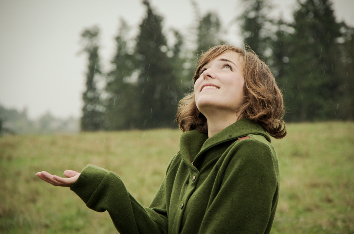 Picture of Morgan looking up to the sky and holding up her hand to check for rain. She is wearing a green Newcastle cardigan.