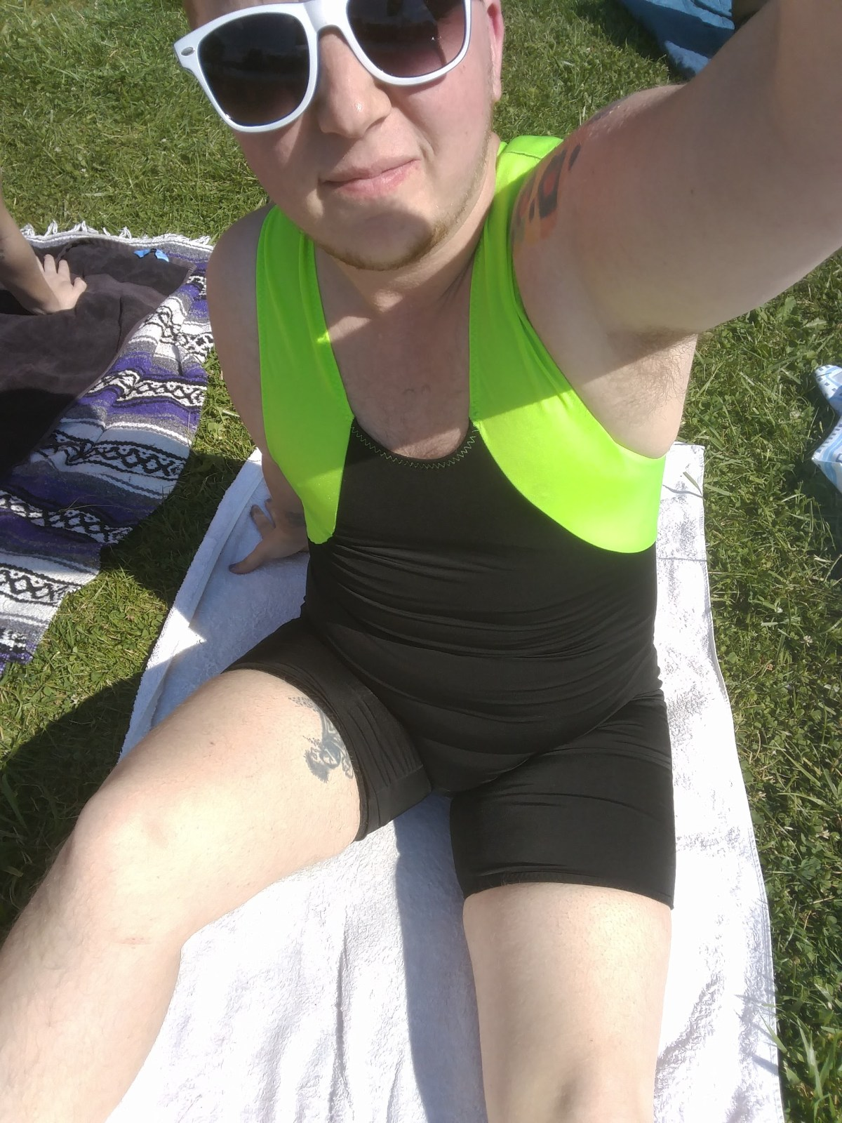 Noah in his swim-singlet at the beach. The bodice is almost entirely black, with a neon green around armscye and into the straps. Has an 80s Body Glove feel to it, paired with white raybans