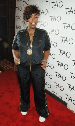 Missy Elliott wears a black shiny short-sleeved track jacket and straight leg pants, both with gold trim.