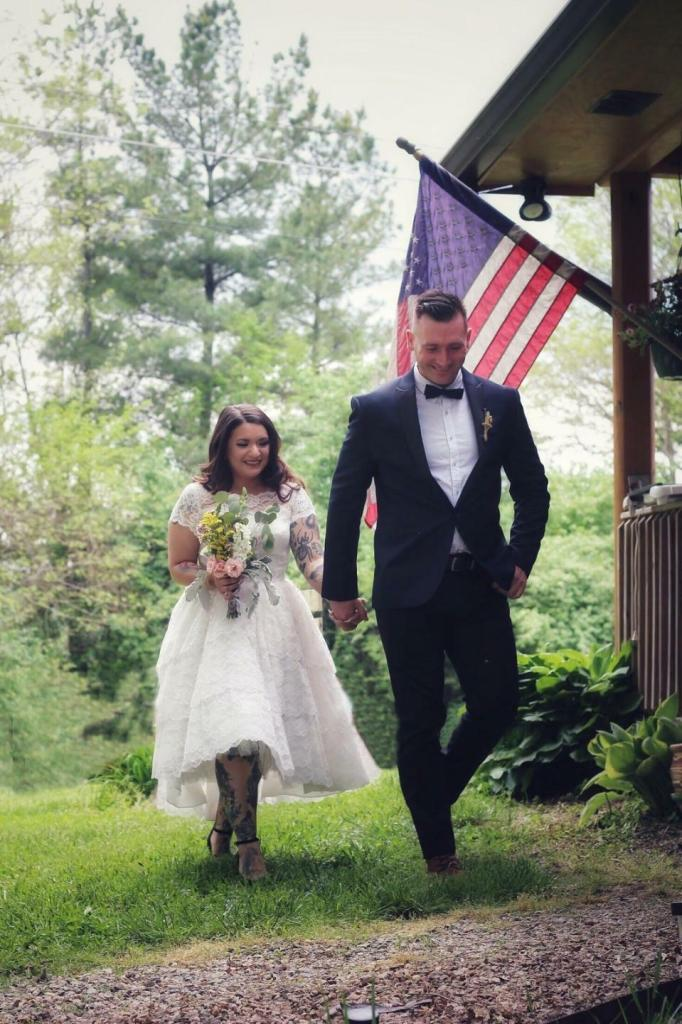 A bride and groom walk hand in hand on the grass past a rustic porch. She is tattooed on her arm and leg, and wears a short-sleeve, boat-necked tea-length gown with lacy overlay.