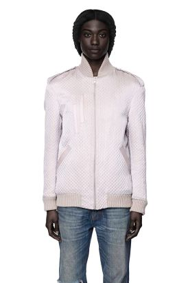 A black model wears a lilac, high-collared bomber jacket in a shiny quilted fabric, and medium-wash jeans.
