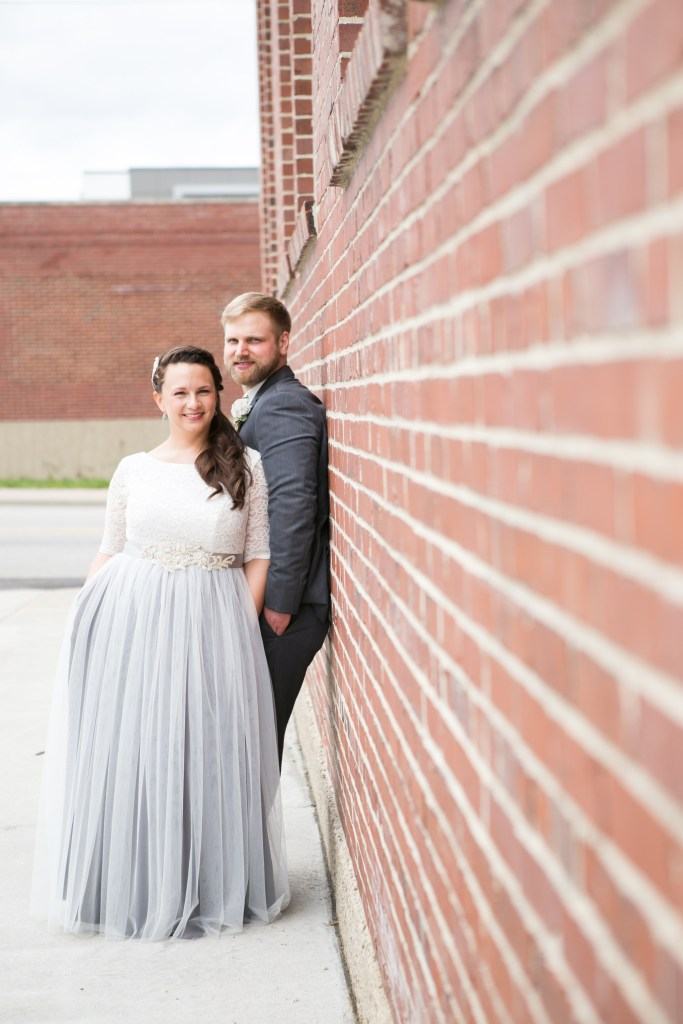 A young couple pose for prom pictures along a brick wall. She wears a gown with a full skirt with pale chiffon overlaying a darker underskirt, an ornate belt, and a fitted lace top with elbow-length sleeves.