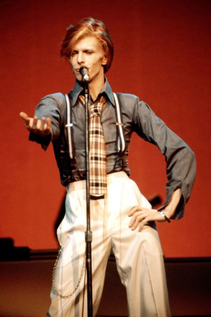David Bowie, a thin white man with red hair, wears a high-collared gray button-front shirt tucked into cream trousers, accessorized with black and white suspenders and a brown plaid tie. He
