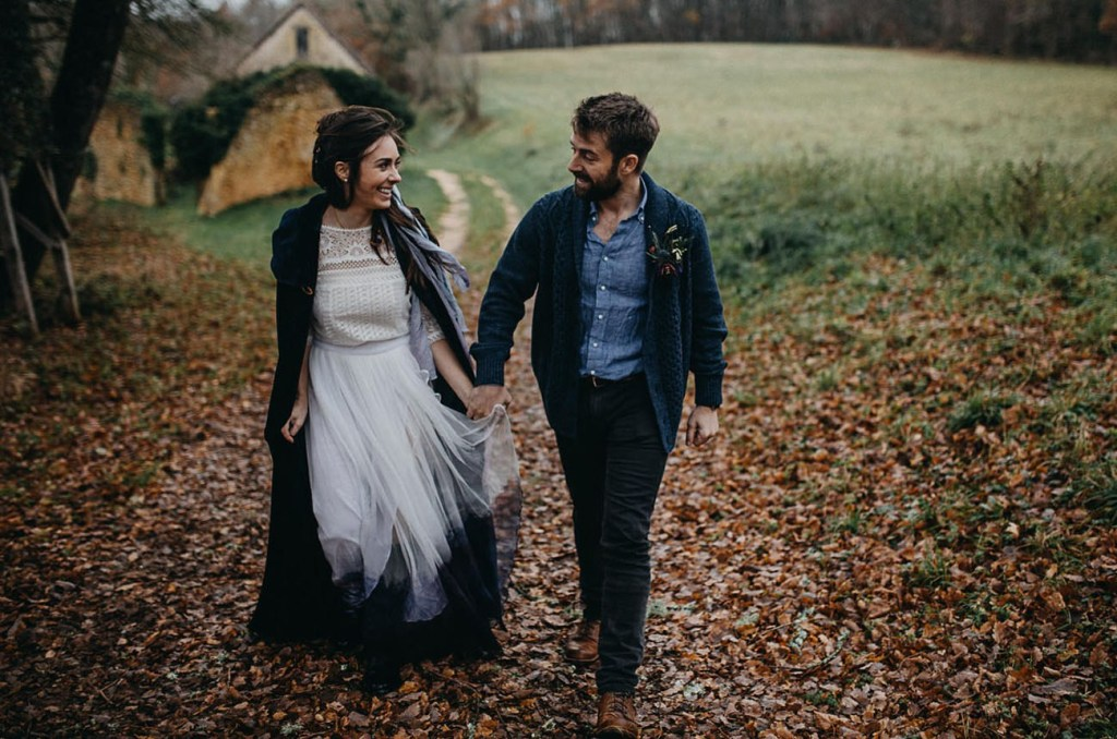 A woman and a man walk through an autumn path covered in leaves. She wears a black floor-length cape, and a white tulle skirt with a white lacy top. He wears a jacket over a chambray shirt and dark trousers.