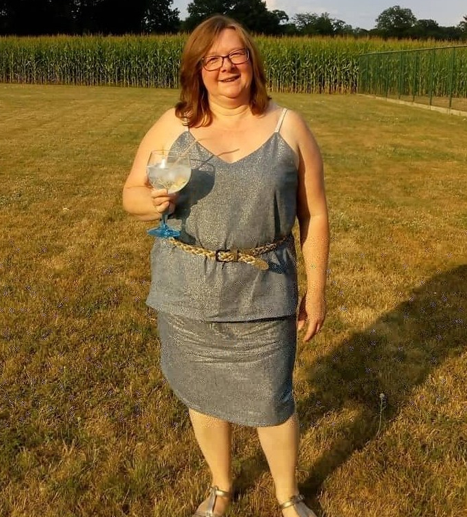 The author wears a sparkly silver-grey linen camisole and skirt, and stands in the sun with a large glass of wine