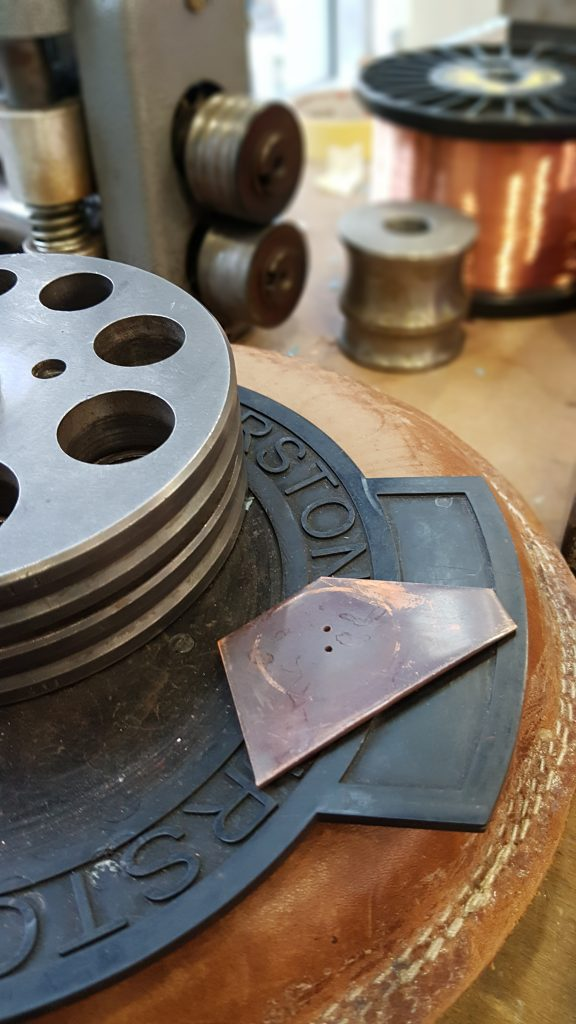 A circular metal punch for cutting out the round buttons. The copper has already been drilled with button holes. All very grubby at this point