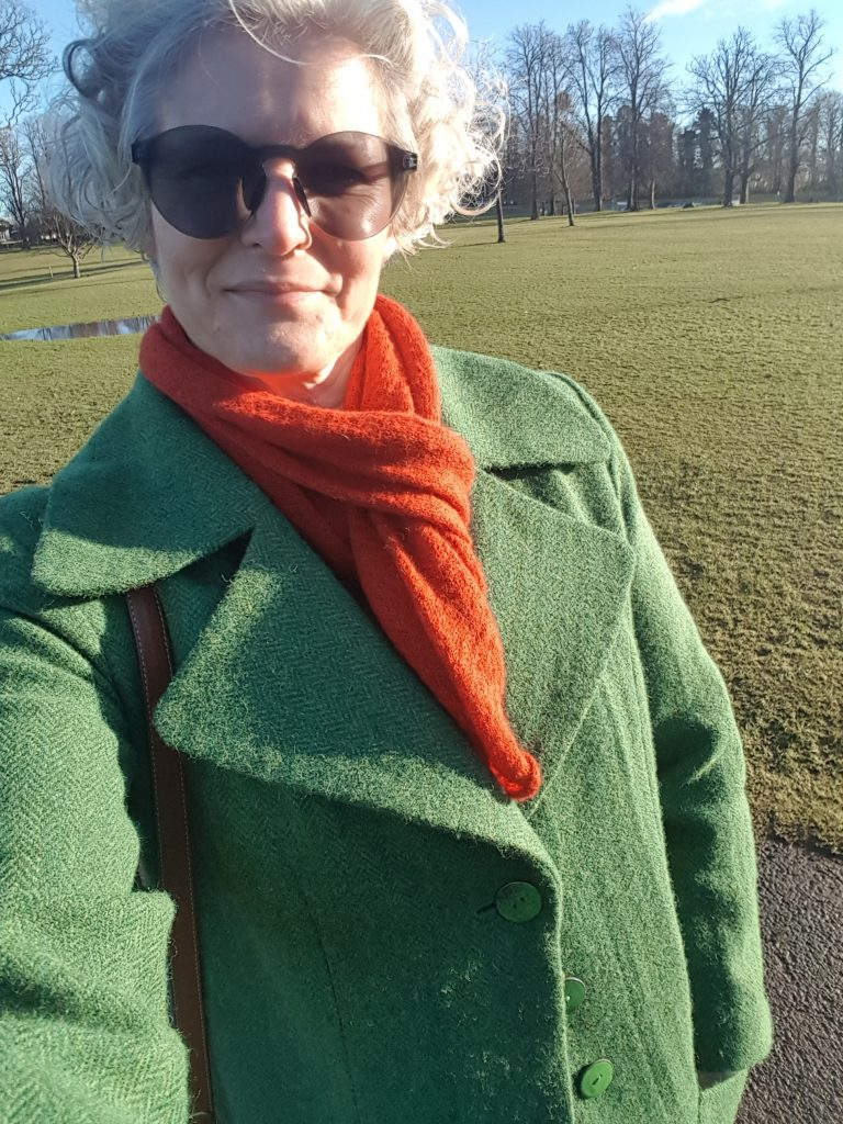 The green coat in action in the park, keeping me warm on a cold day, worn with a burnt-orange scarf and sunglassses