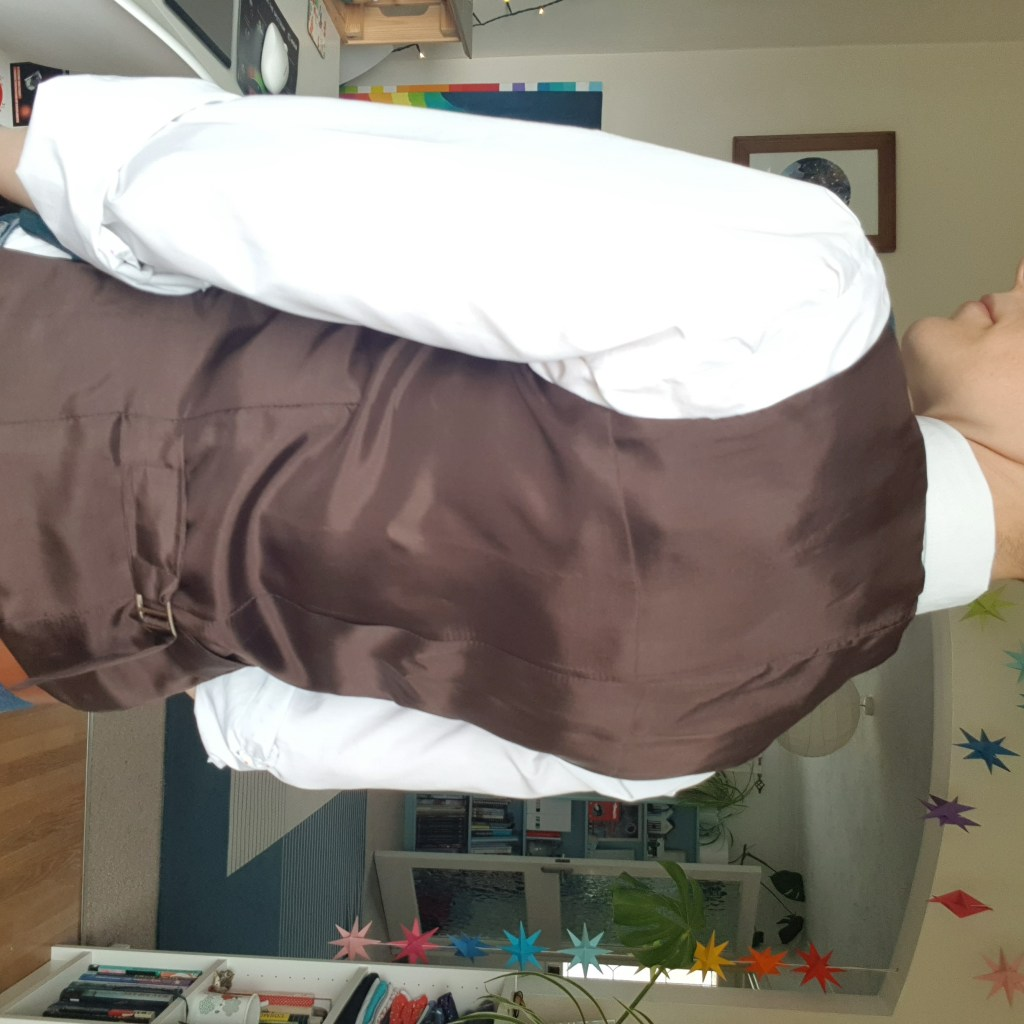 A photo showing the back of the waistcoat, which is brown, worn by the author also wearing a white shirt.