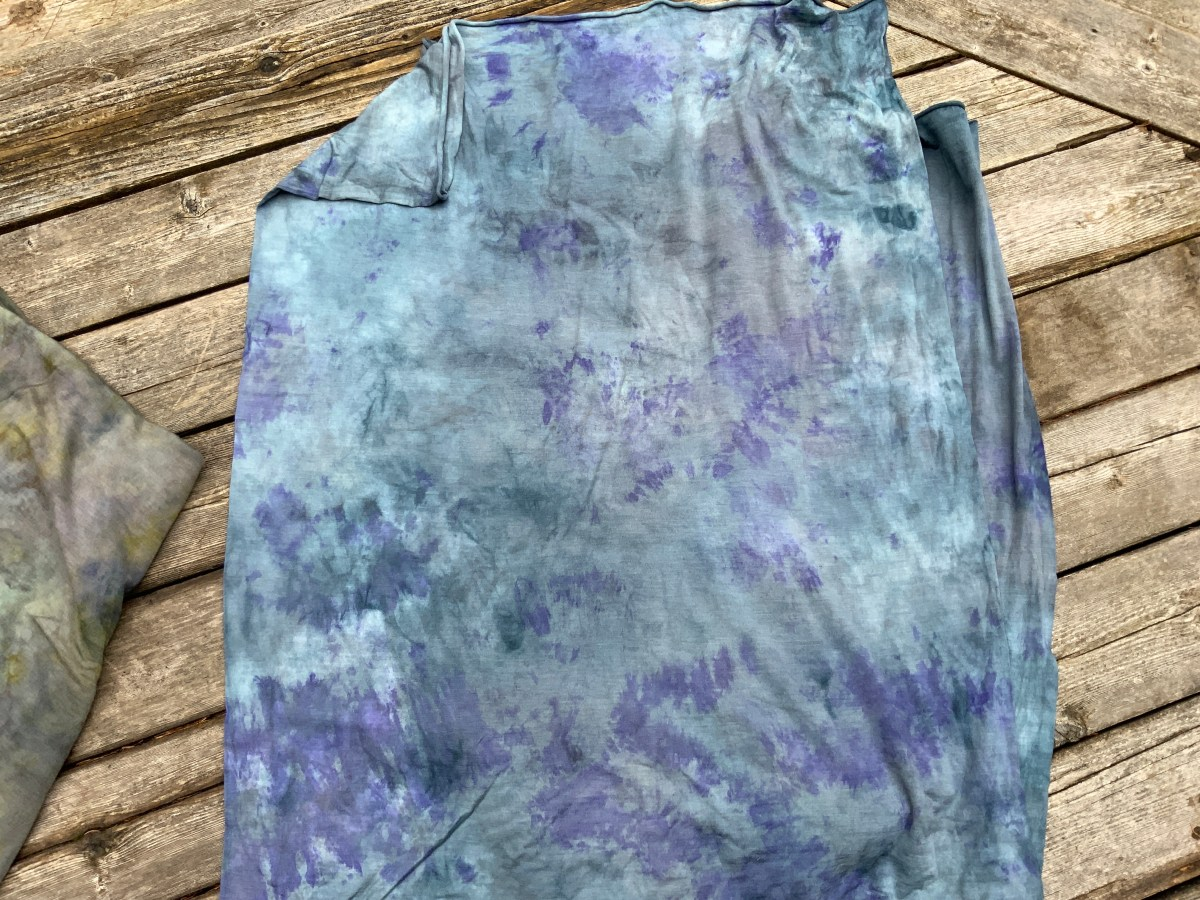 A cut of hand-dyed merino and silk jersey in shades of blue with purple details on weathered hardwood flooring
