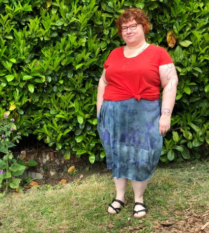 Kim is standing on grassy ground, a background of bright green leaves. Her hair is red and short. She wears glasses with a red frame. She wears a red T-shirt, a skirt with an asymmetrical hem in a merino and silk jersey fabric in blue with dark blue and purple details, and black sandals. The skirt looks drapey and flowy.