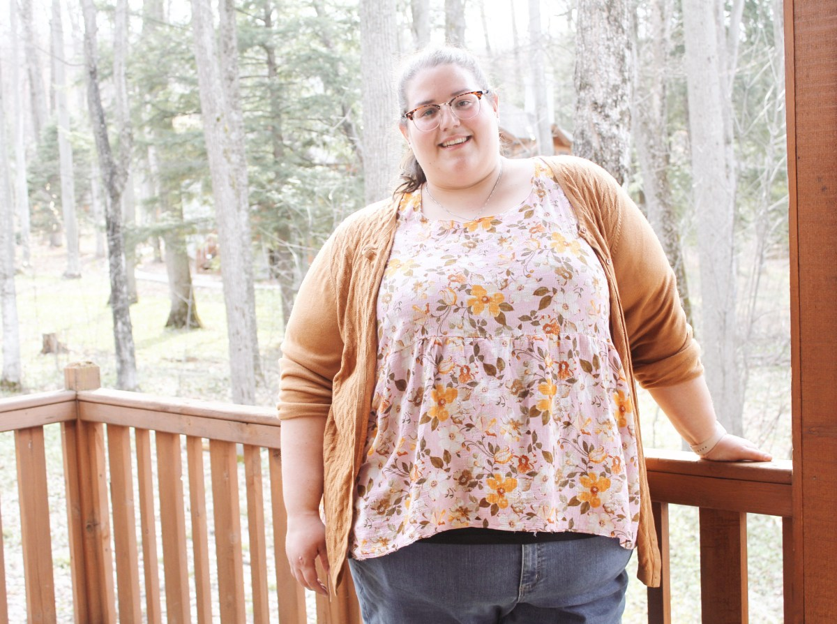 Jenn stands on a deck, facing the camera with woods in the background. She wears blue jeans, a mustard cardigan, and a pink and yellow floral blouse. She smiles proudly at the camera.