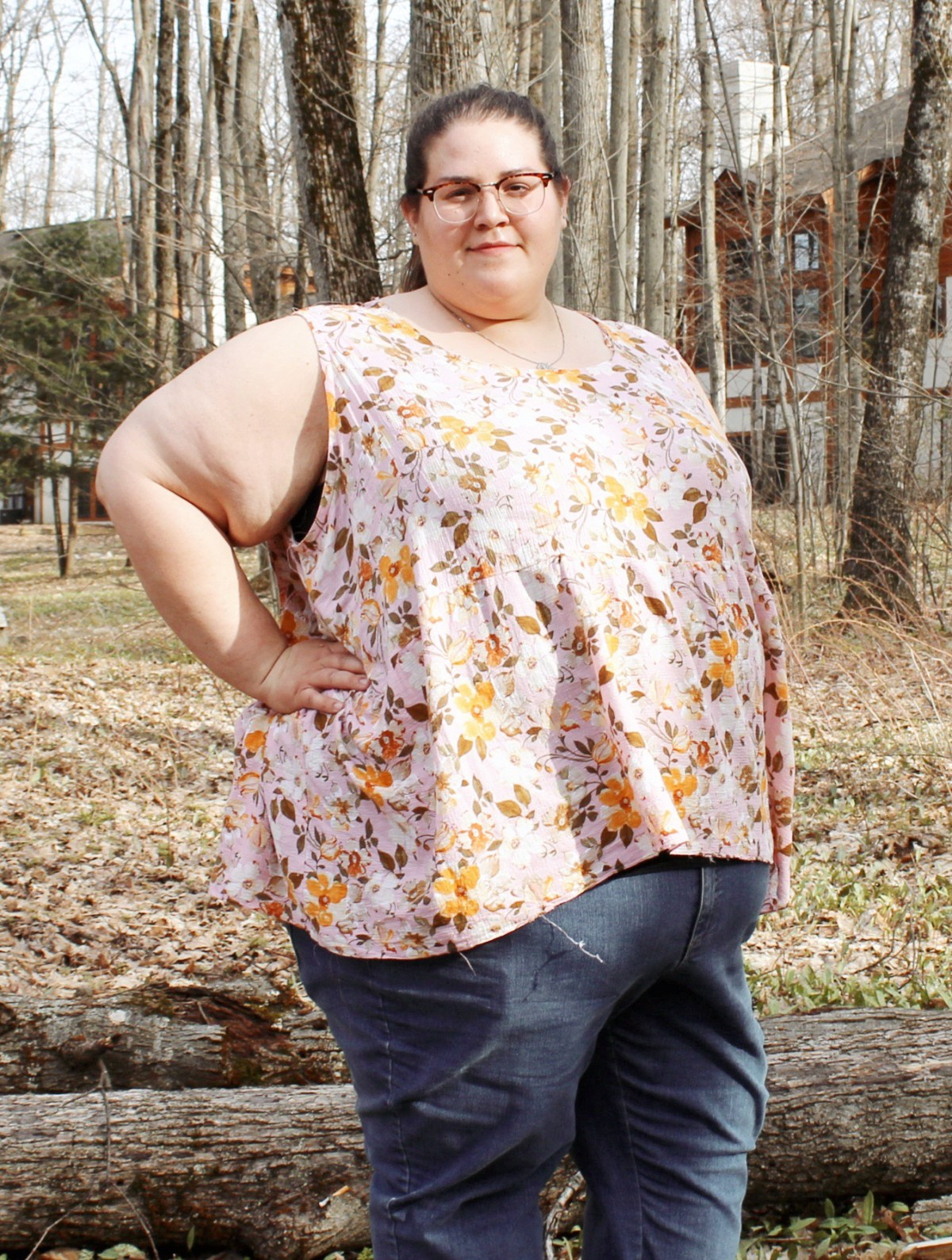 Jenn stands confidently, right hand on her hip, looking at the camera. Some large tree limbs, woods, and a house are behind her. She smiles slightly. Jenn wears blue jeans and a sleeveless pink and yellow floral blouse with a gathered lower bodice. A few loose threads can be seen dangling at the right front hem of the blouse.