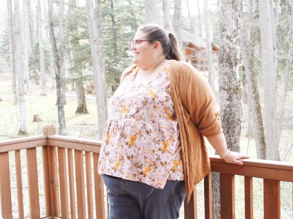 Jenn leans with her back to the deck railing, woods behind her, showing a profile view of her outfit. She wears blue jeans, a mustard cardigan, and a pink and yellow floral blouse with a gathered lower bodice. Jenn smiles.