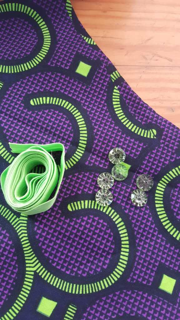 Purple and green fabric with green bias tape and green buttons