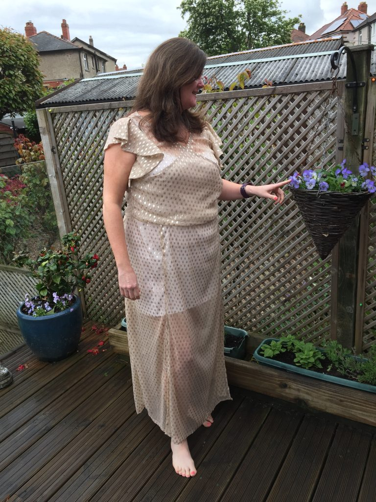 Image shows Louise stood on her deck in bare feet wearing her finished maxi length dress with wrap top and flippy sleeves, looking to the side at a hanging basket of blue flowers