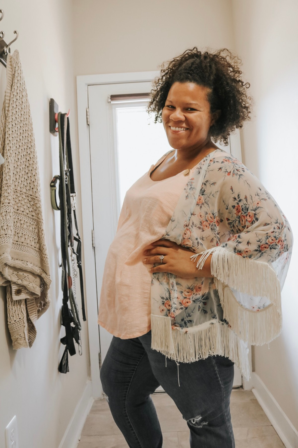 Amanda's photo shows her in profile to the camera, showing off her baby bump! She wears a pale peach sleeveless top with a sheer, floral, fringed duster over top of ripped jeans.