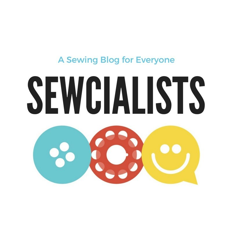 "The Sewcialists logo! The text reads ""A Sewing Blog for Everyone"" and the logo graphic includes the word ""Sewcialists"" in black, with a bright blue button, a coral thread bobbin, and a yellow smiley-face dialogue bubble, all on a white background."