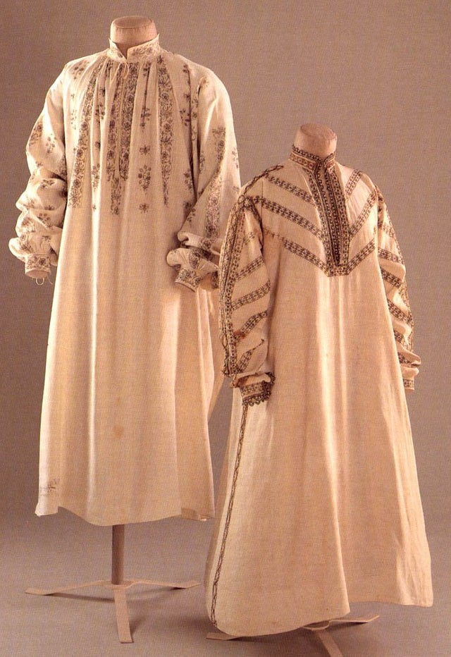 Two mannequins wearing long cream-coloured, heavily embellished robes.