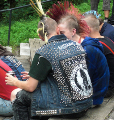 A crowd shot of the audience at a punk concert, from behind, focused on a pair of concert-goers with bleached and dyed spiked hair. The one closest to the camera wears a cut-off denim jacket covered in an anti-nuclear slogan and tightly-packed metal spikes.