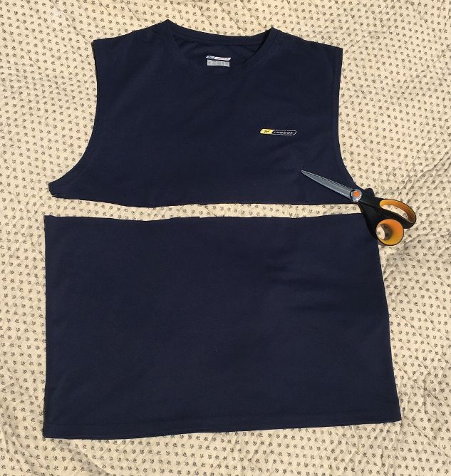 Image of a men's dark blue tank top cut across from armpit to armpit and a pair of scissors.