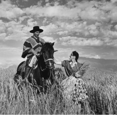 The man on horseback wears a striped poncho. The woman leading the horse carries a large bundle of wheat, which obscures her brightly patterned skirt and her blouse.