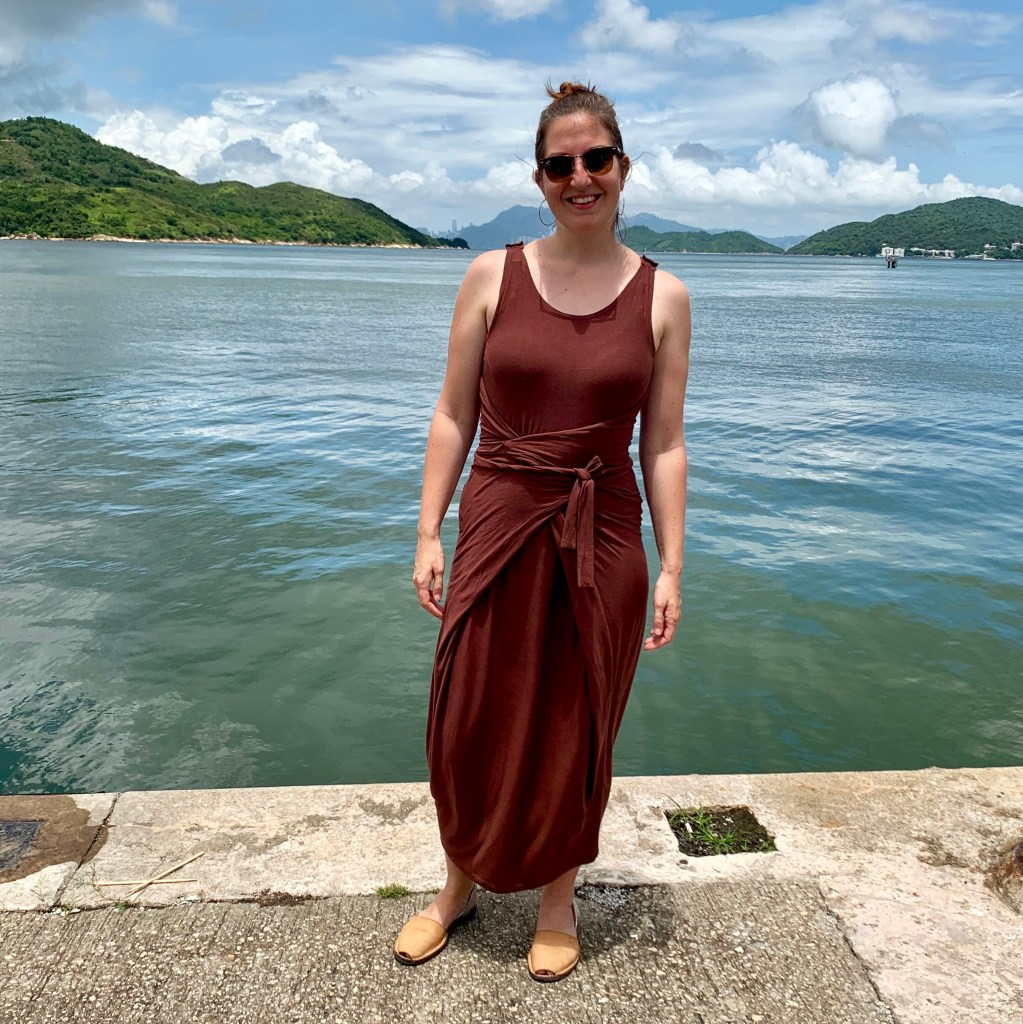 Sophy is wearing a brown dress, standing on the edge of the ferry pier. In the far distance of the picture you can just make out Central Hong Kong.