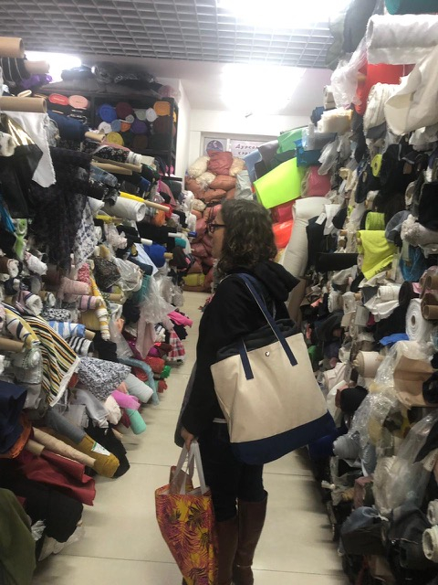 Erin stands in a fabric shop, with fabric bolts piled high around her.