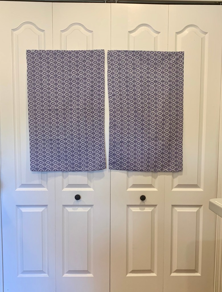 Two blue and white diamond patterned pillowcases taped on a closet door
