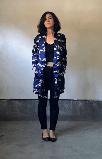 designer in her own Cambria Duster coat made of a blue and white floral, wearing a black tank and black jeans, with an industrial warehouse looking background