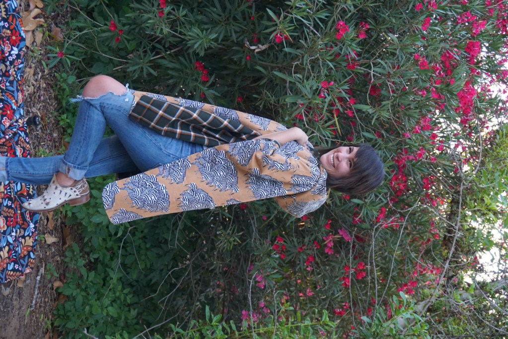 Mary stands in front of a wall of greenery and bright pink flowers, smiling widely. She has turned to her right and has bent her left knee to show off her white and brown ankle boots. Her poncho drapes around her, showing the navy plaid lining and the hood.