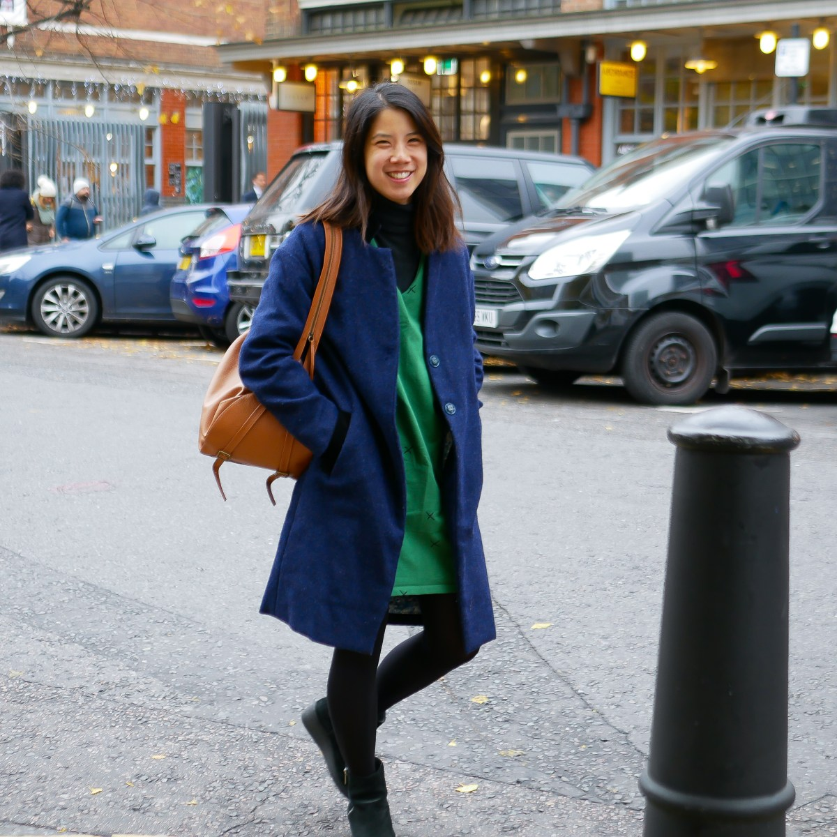 Author in NYC in self made coat and dress, smiling and happy