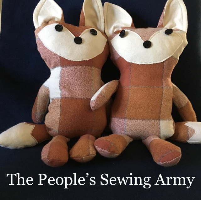 A pair of stuffed animals--foxes!--sit together against a black background. The foxes were donated to The Community Transitional School.