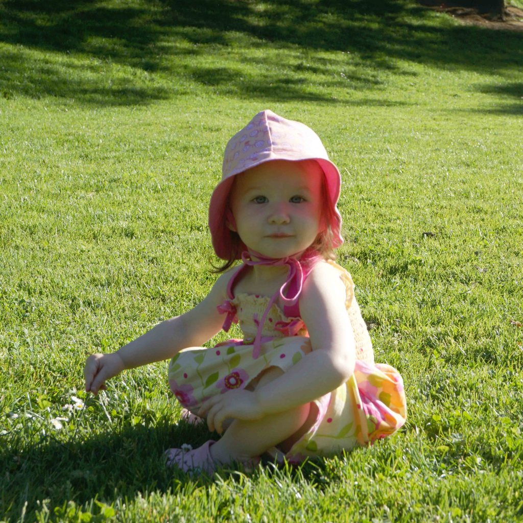 Baby girl in the grass on a sunny day wearing a pink bonnet hat & floral dress sewn by author
