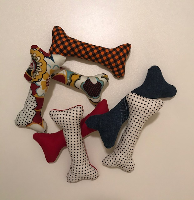 7 dog toys shaped like bones are piled together on a light-colored surface. The bones are stuffed, ready for play time! They are made of scrap fabric in many colors.