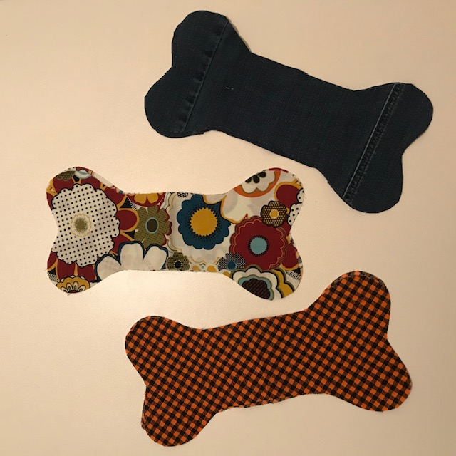 Three unstuffed dog toys shaped like bones are laid flat on a light-colored surface. They are made of scrap fabrics in many colors.