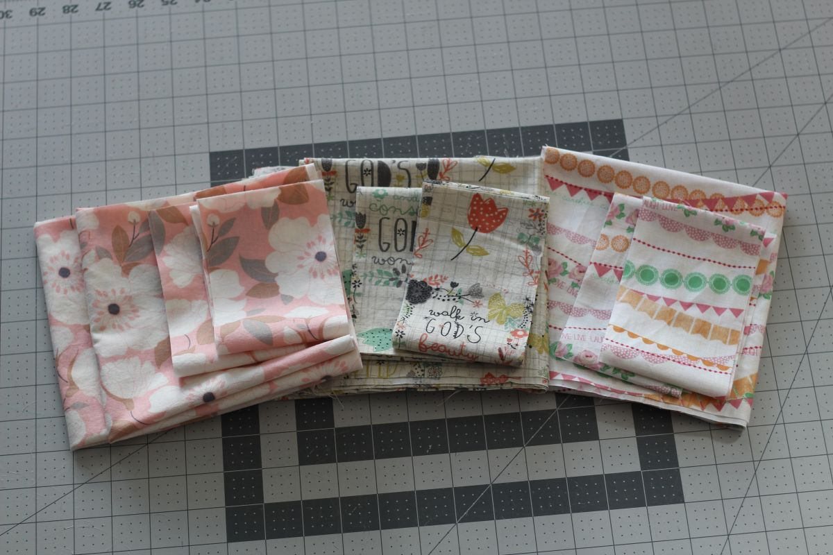 The cut fabric pieces for three tote bags are laid out in neat piles on top of a gray and white grid cutting mat. All three fabrics feature flowers: one is an all-over large scale floral, the second has a few bright red tulips scattered throughout the overall print, and the third has multiple garlands across the fabric, one of which is a flower garland.