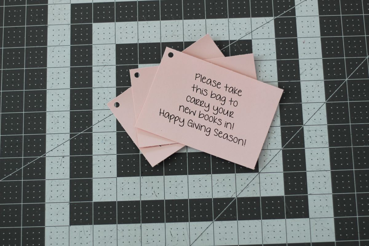 "Three pink tags are stacked on a gray and white grid cutting mat. The tags say, ""Please take this bag to carry your new books in! Happy Giving Season!"""