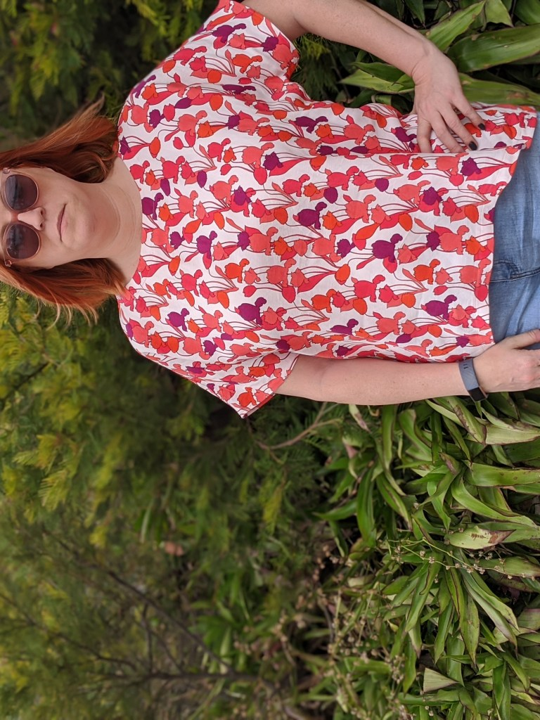 Front of a boxy top with large-scale red print on a white background, modeled on a redhead